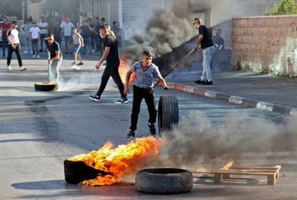 Palestinian youths burn tires in Jerusalem to protest against the march.
