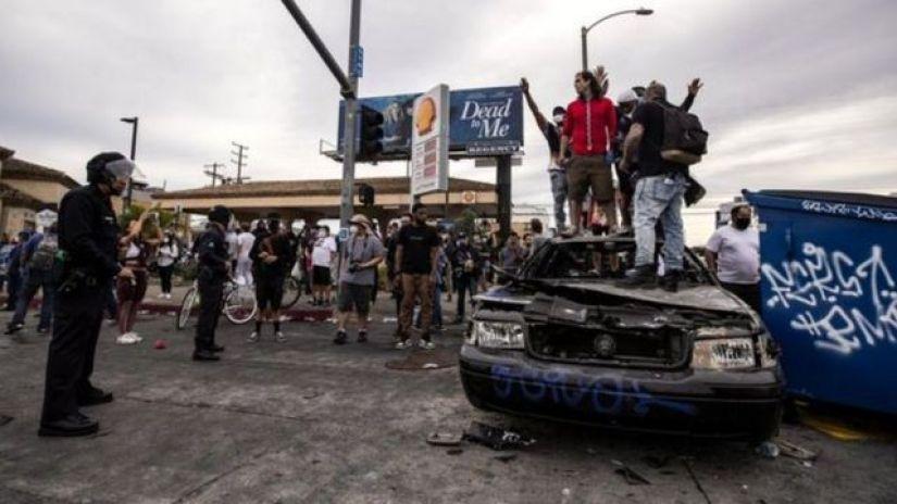 Abigaragambya bahagaze hejuru y'imodoka ya polisi yatwitswe i Los Angeles muri leta ya California