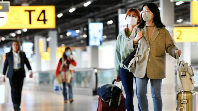 阿姆斯特丹史基浦机场的三名旅客戴着口罩