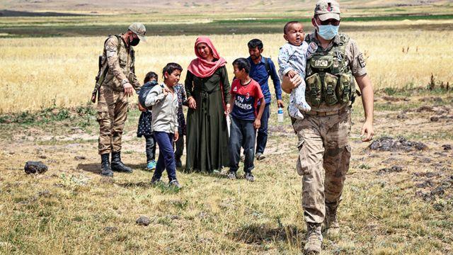 지난 6일 이란 국경을 순찰하는 터키 보안군이 지친 아프간 가족을 돕고 있다