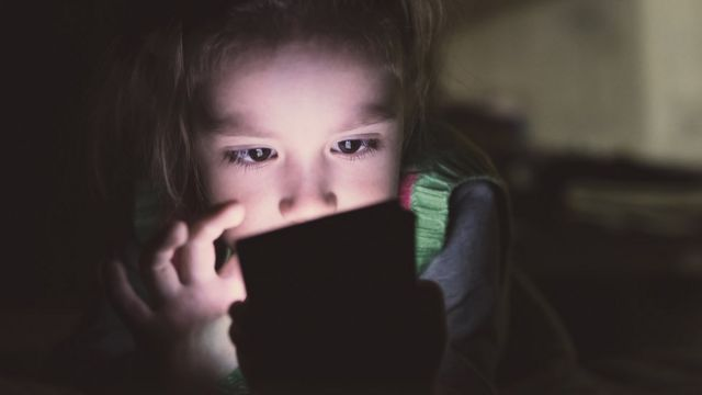 Niña viendo una pantalla a oscuras.