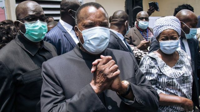 Current Congolese President Denis Sassou Nguesso (C) greets officials after casting his vote in Brazzaville on March 21, 2021.