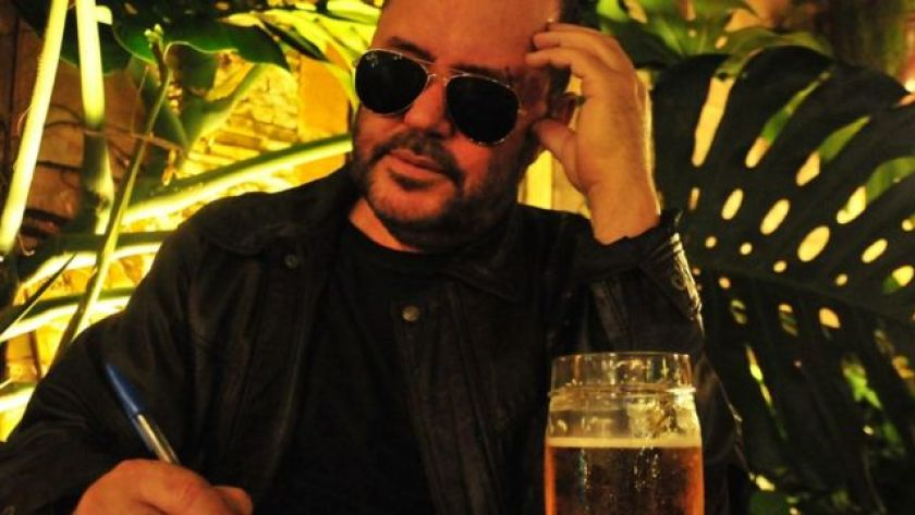 Toninho Geraes sitting at the table, writing and wearing sunglasses
