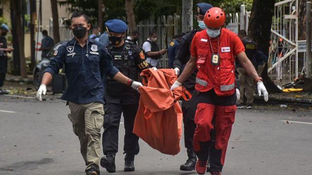Petugas membawa potongan tubuh yang diduga pelaku bom bunuh diri di Gereja Katedral Makasar.