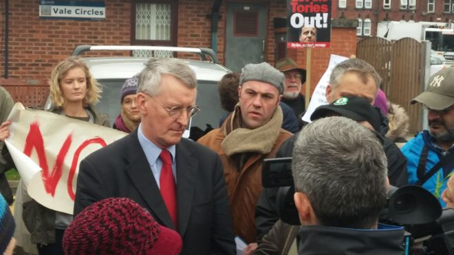 Hilary Benn surrounded by protesters