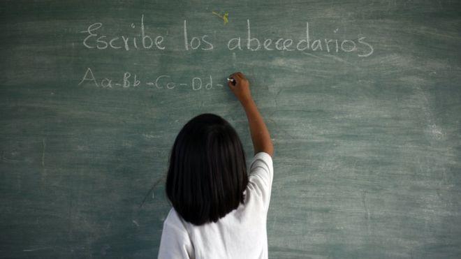 Niña escribe el abecederario