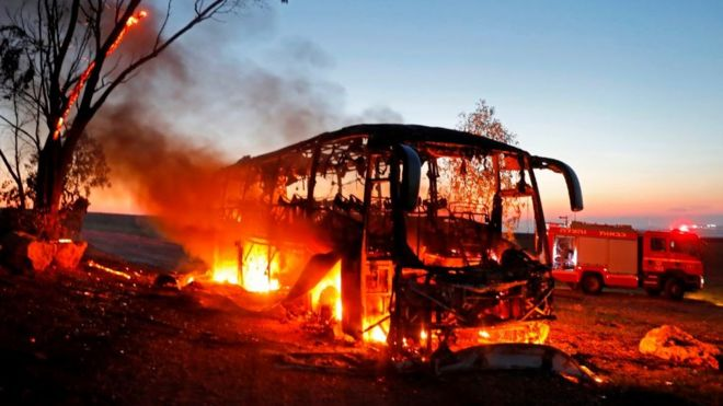 A bus set ablaze after it was hit by a rocket fired from the Gaza Strip, 12 November 2018