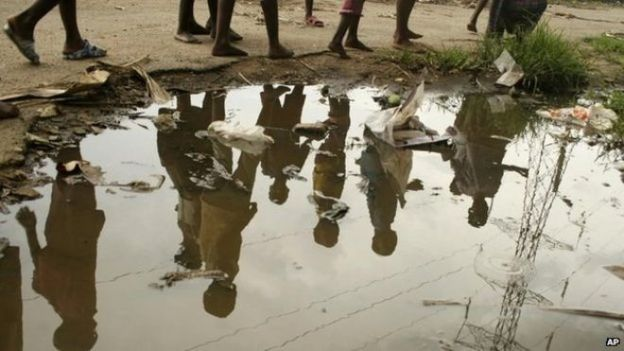 children walk past puddle in harare