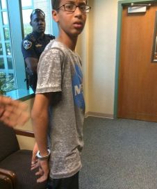 Ahmed Mohamed, 14, waits in handcuffs as a police officer looks on