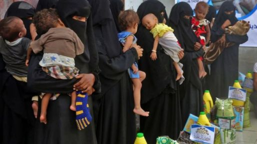 Yemeni women and children wait during food distribution in the province of Hodeida, Yemen, on 30 May 2018