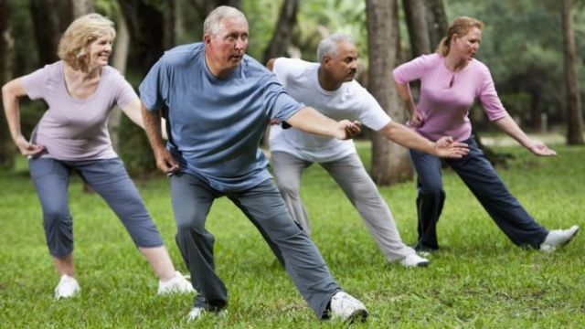 Adults practising tai chi in a park