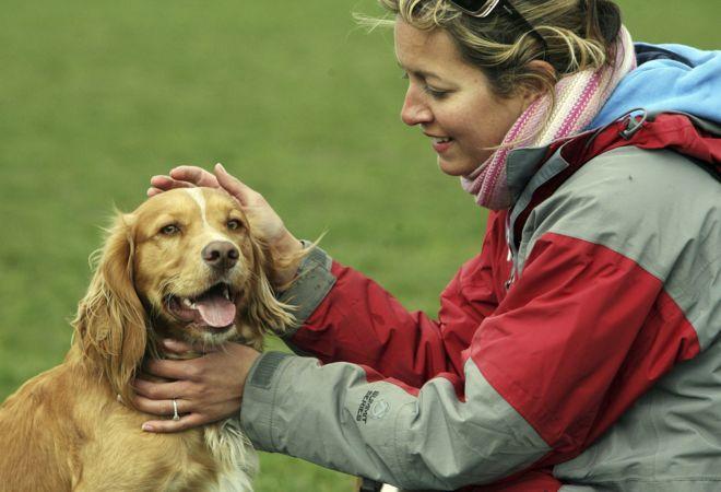 Köpekle poz veren bir kadın