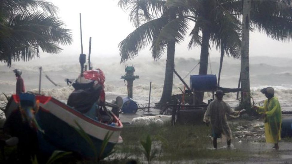 Thai villagers evacuate as high waves are seen in the background