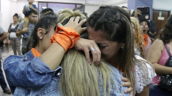 Victims' relatives and campaigners hug each other after a court ruling in Mendoza, Argentina. Photo: 25 November 2019