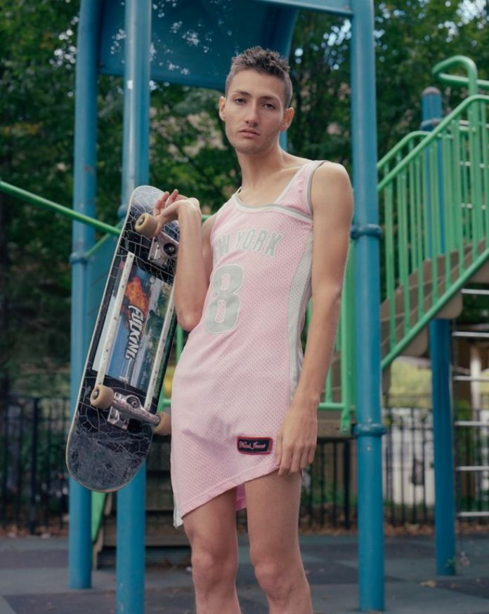 A skateboarder poses whilst wearing a pink sports outfit