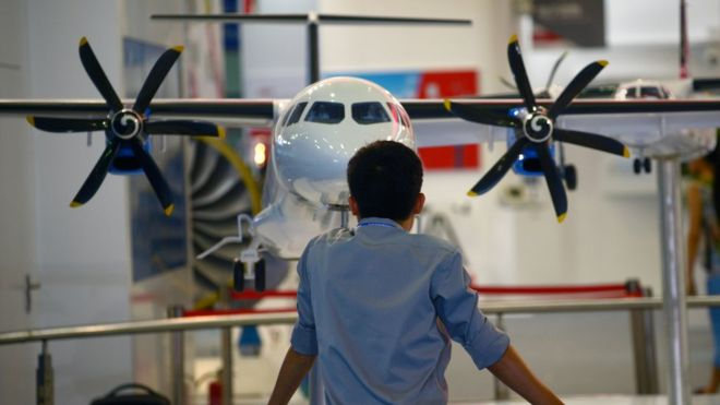 A man looks at an aircraft scale model at the Aviation Industry Corporation of China booth during an expo in Beijing in 2015