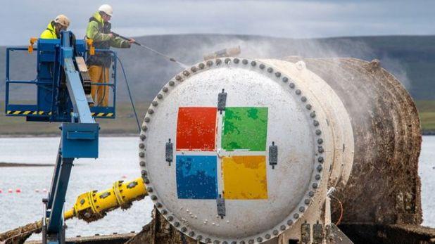 Dos hombres lavan a presión el exterior de la cápsula del centro de datos de Microsoft.