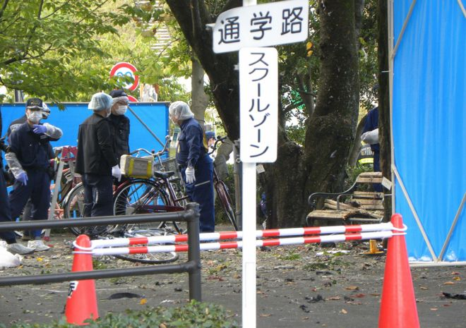 policemen investigate an explosion site at a park in Utsunomiya on October 23, 2016.