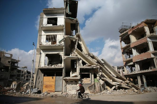 A man cycles past a damaged building in the rebel-held Damascus suburb of Douma (30 December 2016)