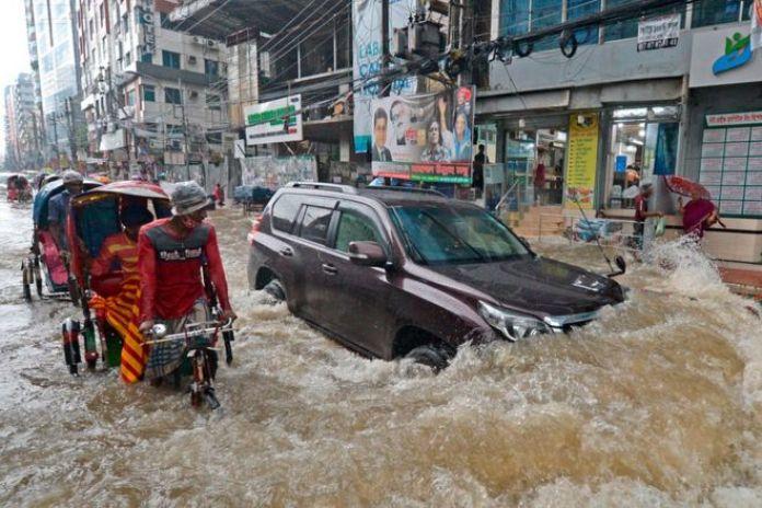 Les banlieusards se frayent un chemin dans une rue inondée