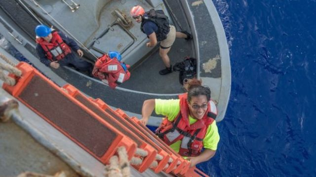 Tasha Fuiaba, uma velejadora dos EUA que navegava há cinco meses em um veleiro danificado, subindo a bordo do USS Ashland no Oceano Pacífico, em 25 de outubro de 2017