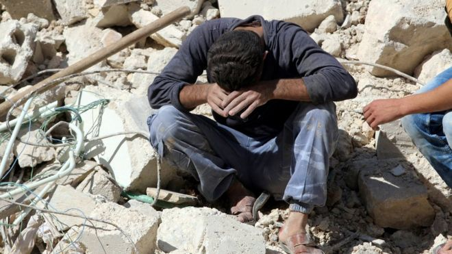 A man sits on rubble after learning of the deaths of relatives in a reported government air strike in the rebel-held Qaterji district of Aleppo (11 October 2016)