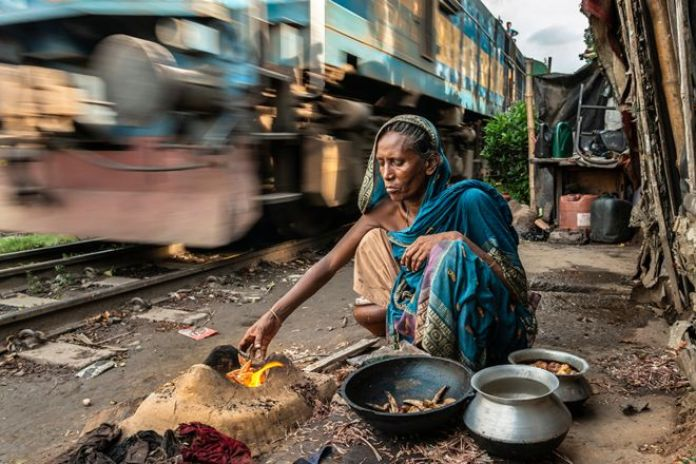 A woman cooks a meal over a fire as a train hurtles by behind her