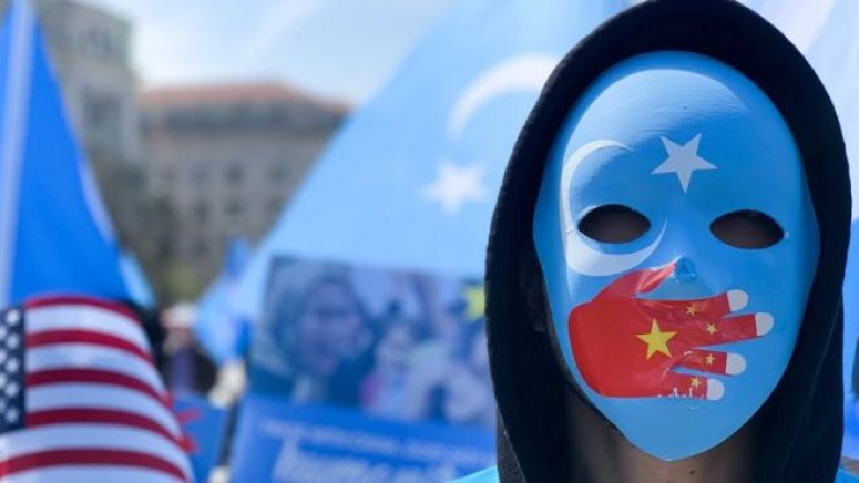 A demonstrator, wearing a mask with a Chinese flag on a hand over the mouth, protests in Washington