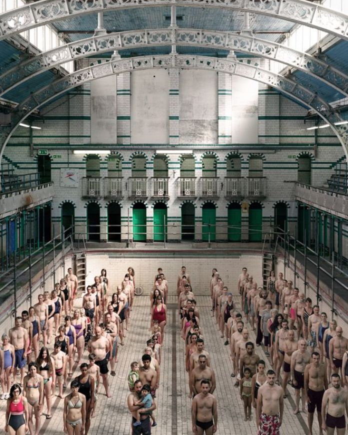 Dozens of swimmers stand on the bottom of an empty indoor swimming pool