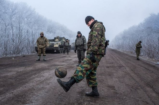 Ukrainian soldiers play football on the road leading to the embattled town of Debaltseve, 15 February 2015