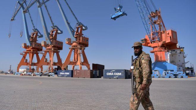 Grúas del puerto con un militar paquistaní armado controlando el área.