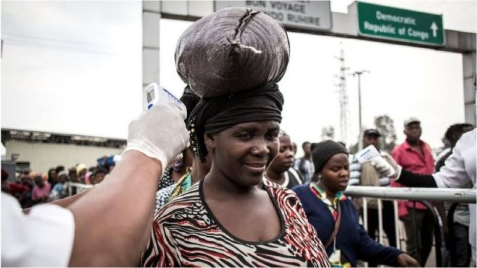 A woman gets her temperature measured at an Ebola screening station as she enters Rwanda from the Democratic Republic of the Congo