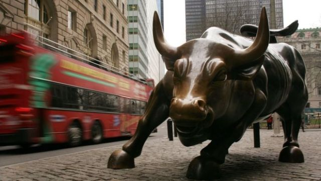 A tour bus passes the Wall Street bull in the financial district in New York City.