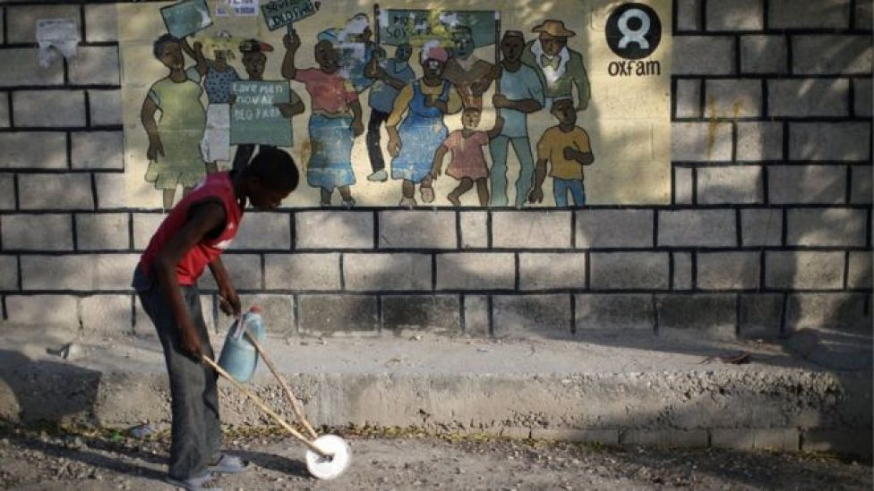 A boy playing with a homemade toy walks past an Oxfam sign in Port-au-Prince, Haiti,
