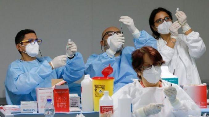 عاملون صحيون يعدون جرعات من لقاحي فايزر وبيونتيك في إيطاليا