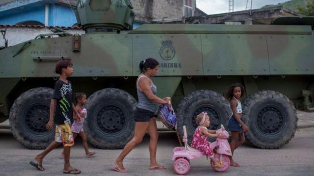 Família com crianças passa em frente a veículo militar