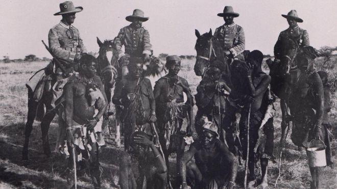 Prisioneiros herero acorrentados, na companhia de soldados alemães montados