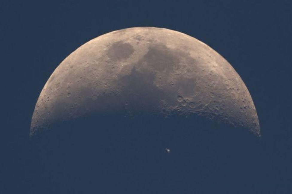 صورة لمحطة الفضاء الدولية أثناء دورانها حول الارض قبالة القمر