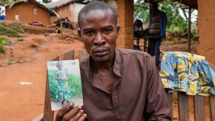 Abdula holds a picture of his daughter
