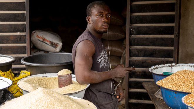 A Nigerian man poses next to some rice in his shop at Ajara Market in Badagry, near Lagos, on 6 September 2019