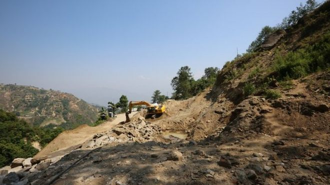 A digger clears a landslide in Nuwakot district