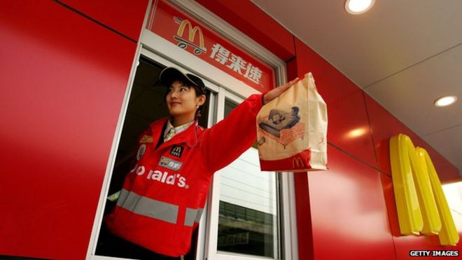 A McDonald's employee hands out food as she waits on customers at their new drive-thru facility on 19 January 2007 in Beijing, China.