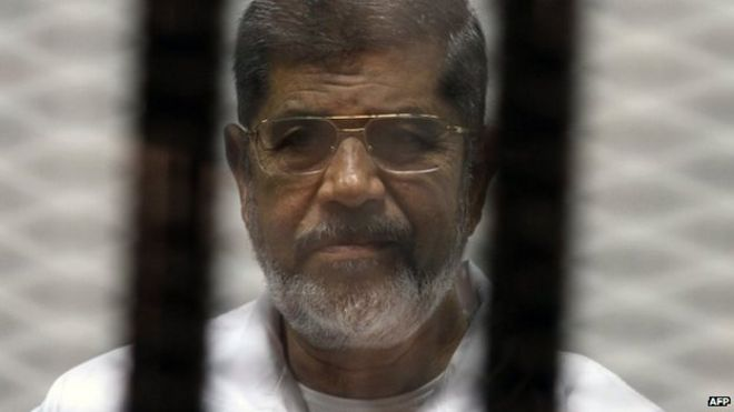File photo: Egyptian ousted Islamist president Mohammed Morsi looking on from behind the defendants cage during his trial, 8 May 2014