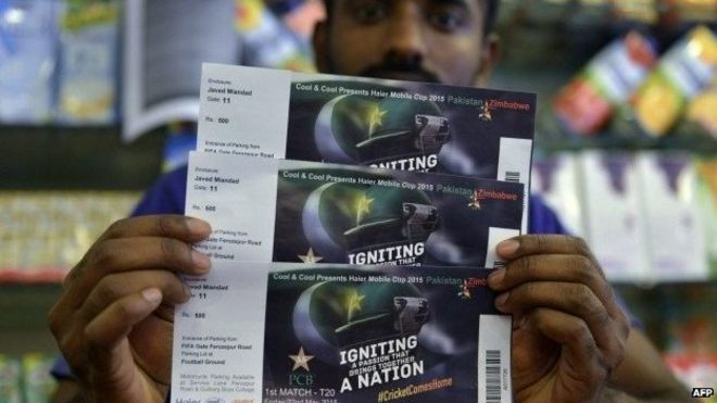 In this photograph taken on May 16, 2015, a Pakistani shopkeeper poses with tickets for the forthcoming Pakistan and Zimbabwe cricket series at a shopping mall in Lahore.