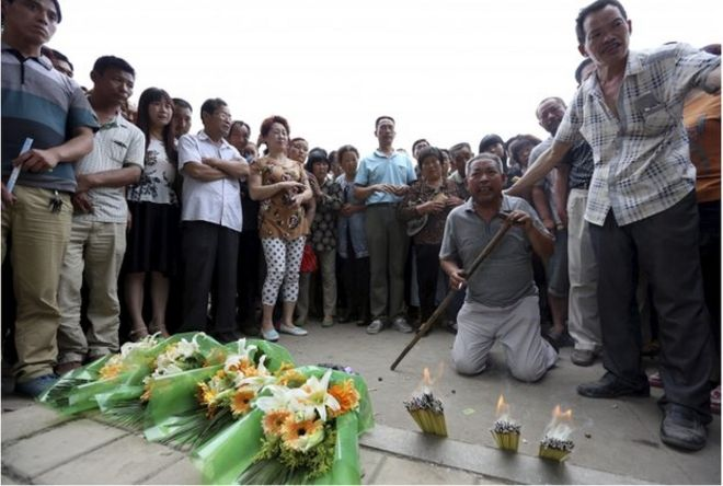 A relative of a victim cries in front of flowers and burning incense as people mourn the victims who were killed during a fire at a rehabilitation centre for the elderly in Lushan county, Henan province, China, 26 May 2015.
