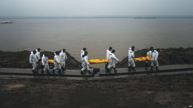 People carry the bodies of the victims of the capsized Chinese cruise ship