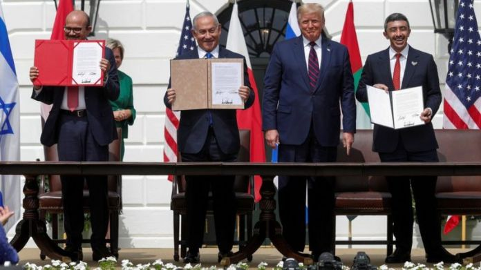 Bahraini Foreign Minister Abdullatif bin Rashid Al-Zayani, Israeli Prime Minister Benjamin Netanyahu and United Arab Emirates Foreign Minister Sheikh Abdullah bin Zayed display their copies of the Abraham Accords as US President Donald Trump looks on, at a ceremony at the White House (15 September 2020)