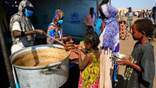 Ethiopian refugees who have fled the Tigray conflict, receive food at a transit centre in Sudan's border town of Hamdayit on November 27, 2020.