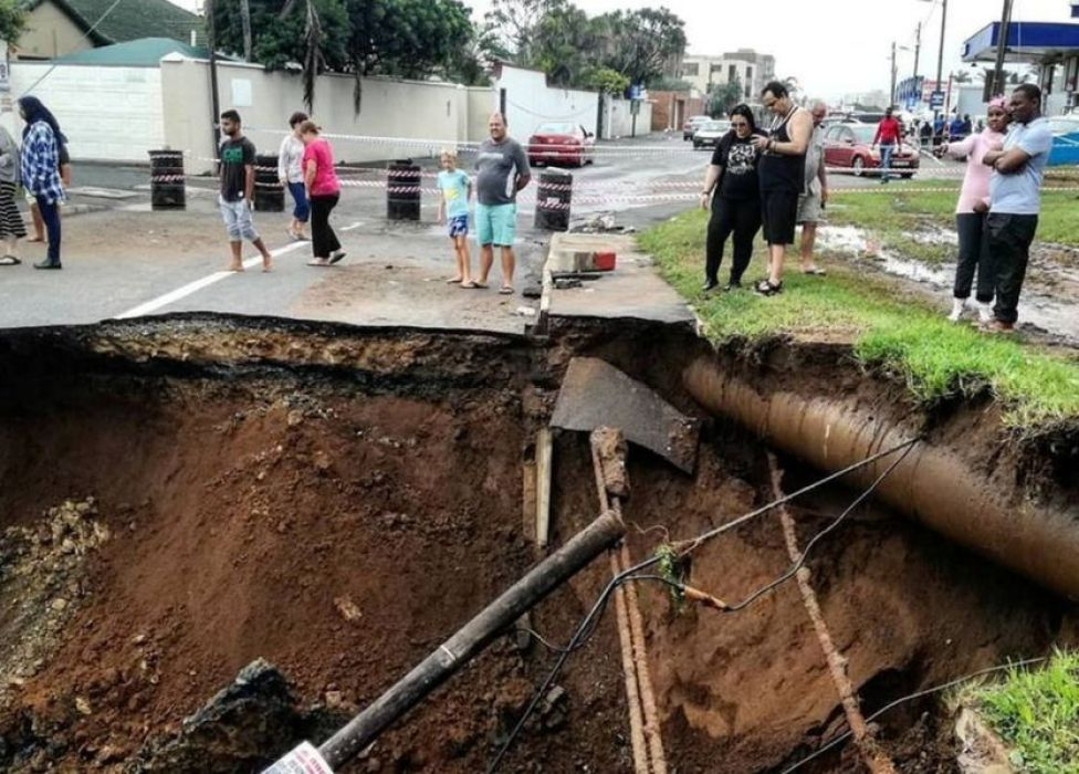 People stand on a damaged road after massive flooding in Amanzimtoti, near Durban, South Africa April 23, 2019