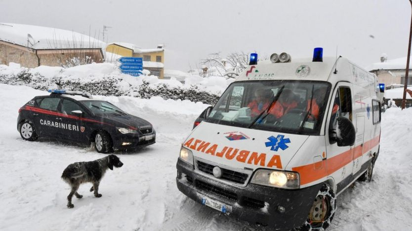 An ambulance drives in Campotosto village covered with snow